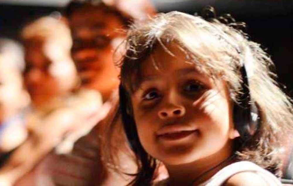 A menina Estefany é cega e acompanhou uma peça de teatro pela primeira vez graças ao fone de ouvido com audiodescrição.